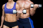 Bodybuilding couple posing with large dumbells on black background