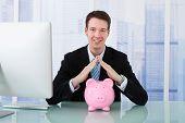 Businessman Protecting Piggy Bank At Desk