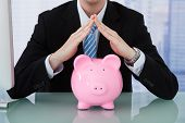 Businessman Protecting Piggy Bank At Desk