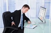 Businessman Suffering From Backache At Computer Desk