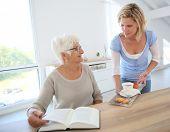 Home helper giving tea to elderly woman