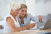 Homehelp with elderly woman using smartphone