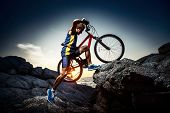 stock photo of ascending  - Bicycle rider crossing rocky terrain at sunset - JPG