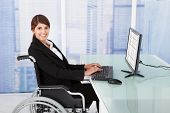 Businesswoman Using Computer While Sitting On Wheelchair