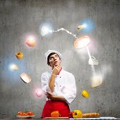 Young thoughtful cook and ingredients flying in air