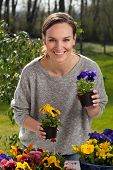 Happy Woman Holding Pots With Pansy Flowers