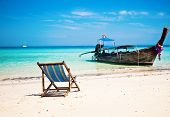 Exotic beach holiday background with beach chair and long tail boat - Thailand ocean landscape