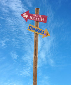 pic of nudist beach  - wooden arrow direction signs post to the nude beach and showers against a blue sky - JPG