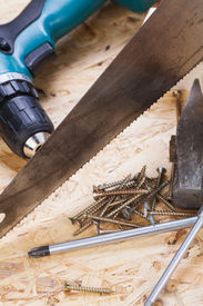 image of joinery  - Battery-operated portable hand drill with timber screwdrivers and screws surrounded by fresh wood shavings in a carpentry joinery DIY or construction concept