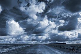 foto of cloudy  - Empty asphalt country road under dark dramatic cloudy sky - JPG