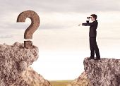 Businessman standing on the edge of mountain with a rock question mark on the other side