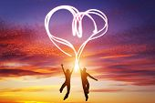 image of happy day  - Happy couple jump together and make a heart symbol of light manifesting their love - JPG