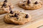 foto of chocolate-chip  - close up of a home made chocolate chip cookie on a wooden cutting board