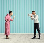 quarrel between dissatisfied wife and angry husband with megaphone