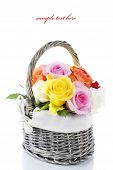 stock photo of flower arrangement  - Multicolored roses in a basket over white  - JPG
