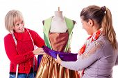 image of dress mannequin  - two happy seamstresses working on a dress on a mannequin isolated over a white background - JPG