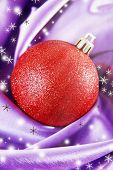 Beautiful Christmas ball on purple satin cloth