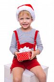 Little blond kid in red costume of dwarf holding gift box with ribbon. Christmas