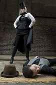 stock photo of ripper  - Woman dressed as Jack the Ripper on top of man lying on the ground.