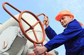 picture of turn-up  - Worker turns big gas valve against sky bottom view close - JPG