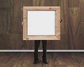 Businessman Holding Blank Whiteboard With Wood Frame In Wooden Room