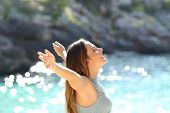 foto of breathing exercise  - Happy woman breathing fresh air raising arms on holidays with a tropical sea in the background - JPG