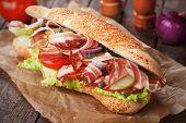 Submarine sandwich with bacon, caper, tomato and lettuce salad