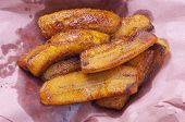 stock photo of grease  - Sliced greasy fried plantain bananas on pink paper to soak up excess grease - JPG