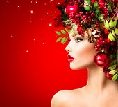 Christmas Winter Woman. Beautiful New Year and Christmas Tree Holiday Hairstyle and Make up. Beauty Fashion Model Girl over holiday red Background. Creative Hair style decorated with Baubles. Makeup