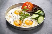 Fired eggs presentation with mints, tomato, olive, cucumber and sumac served for breakfast