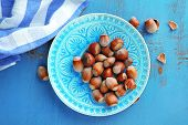 Hazelnuts on plate on wooden background