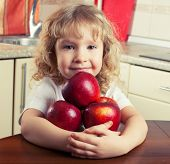 Child eating fruits. Girl at kitchen with apple