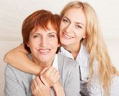 Mother with daughter at home. Happy women sitting at sofa. Family