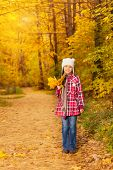 Cute Asian girl with bunch of yellow leaves alone
