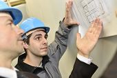 Supervisor with construction worker checking blueprint