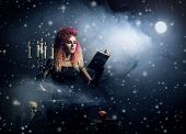 Beautiful witch making witchcraft over winter background