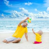Baby and father on the tropical beach playing toy plane
