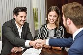 stock photo of married couple  - Smiling young couple shaking hands with an insurance agent or investment adviser - JPG