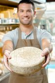 image of meals wheels  - Man holding a wheel of cheese - JPG