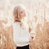 foto of pullovers  - Portrait of a beautiful blonde girl in a field in white pullover smiling with eyes closed concept beauty and health - JPG
