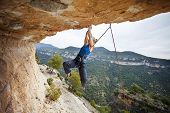 pic of struggle  - Woman rock climber struggling to make next movement up - JPG