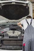 pic of car repair shop  - Rear view of male engineer repairing car in automobile repair shop - JPG