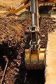 stock photo of backhoe  - A backhoe and crew dig a utility trench for gas and other electrical utilities at a new commercial construction development - JPG