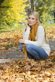 stock photo of full cheeks  - Full length of thoughtful young woman crouching on steps in park - JPG