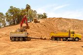 stock photo of dump_truck  - Large track hoe excavator removing top soil and loading into a tandum dump truck at a new commercial development construction site - JPG