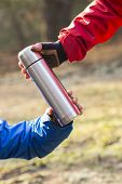 picture of coffee crop  - Cropped image of hikers holding insulated coffee container in forest - JPG