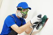 image of breather  - Home improvement plasterer worker in protective mask and glasses working with sander for smoothing wall surface - JPG
