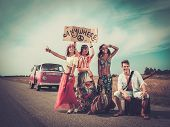 image of hippy  - Multinational hippie hitchhikers with guitar and luggage on a road - JPG
