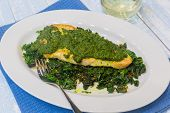 stock photo of sauteed  - Sauteed fish topped with pesto on a bed of sauteed kale - JPG
