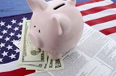 pic of income tax  - USA Tax Day concept with income tax form and cash on stars and stripes flag with piggy bank - JPG